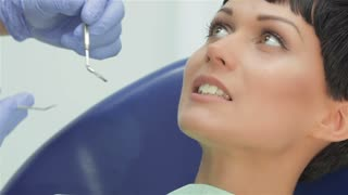 Dentist teeth carefully examines the patient girl
