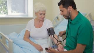 Doctor measures blood pressure of senior woman