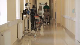 Doctor pushes wheelchair with patient at the hospital