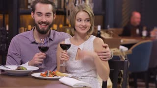 Engaged couple with wine glasses in restaurant
