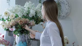 Female florist arranges flowers in vases at flower shop