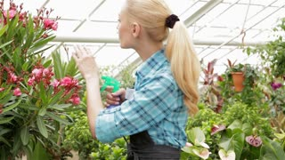 Female florist sprays water on plants at the garden centre