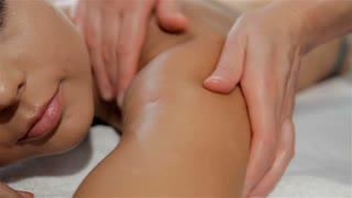 Female hands massages client's arm