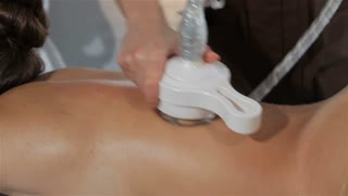 Female hands moves the head of massage machine along the girl's back