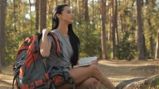 Female hiker removes her backpack from shoulders