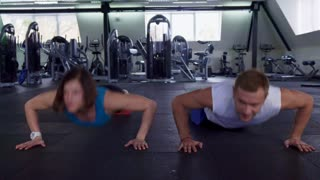 Fitness man and woman doing push ups at the gym. Sportsman and sportswoman synchronously raising and lowering their bodies using their arms. Male and female athletes exercising against background of
