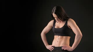 Fitness woman demonstrates her trained belly