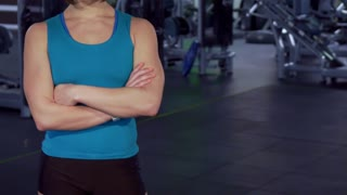Fitness woman keeping her arms crossed on her chest at the gym. Pretty female athlete standing against background of different exercise equipment at the fitness center. Camera sliding from bottom up