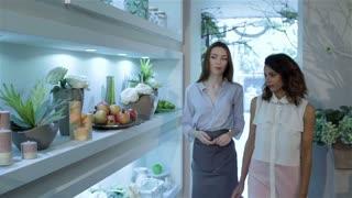 Florist shows design compositions to her client at flower shop
