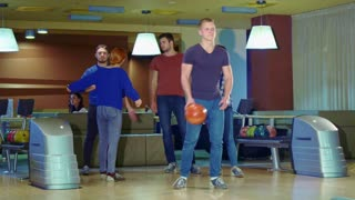 Friends high-fiving blond man after his release at the bowling. Attractive caucasian boy rolling red ball. Young people spending time together at the bowling alley