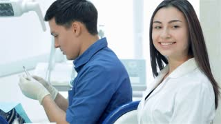 Girl assistant sitting next to a dentist and smiling directly at the camera, then thumb up