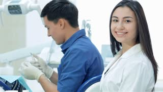 Girl-assistant sitting next to a dentist and teeth smile directly at the camera