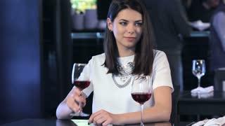 Girl drinks wine at the restaurant