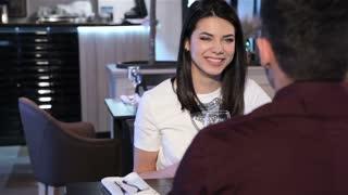 Girl flirts with her boyfriend at the restaurant