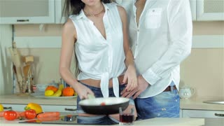 Girl shows her boyfriend tomatoes in a frying pan