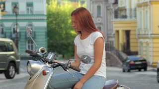 Girl sitting on scooter in european city