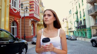 Girl walking in the town with go cup