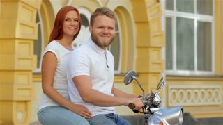 Glamorous couple riding a vintage scooter