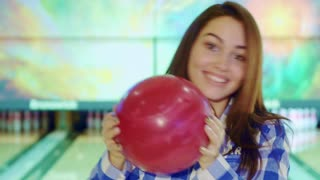 Gorgeous brunette girl holding bowling ball near her face. Pretty female bowler smiling for the camera. Close up of cheerful caucasian lady dressed in checkered shirt