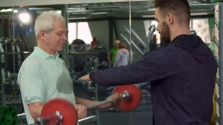 Gray senior man training his bicepses at the gym. Aged male sportsman making curls with barbell. Young caucasian trainer advicing his client about exercise
