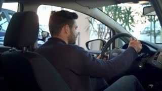 Handsome brunette man showing his thumb up inside the car. Attractive bearded guy approving the car at the dealership. Young male driver turning his face to the back seat