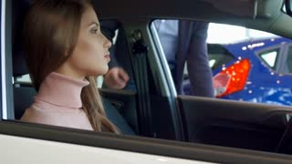 Handsome brunette man sitting on the driving seat. Attractive bearded guy joining his girlfriend inside the car. Close up of pretty caucasian girl looking at her boyfriend