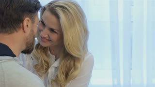 Handsome brunette man telling something to his wife at home. Close up of pretty blond woman touching the face of her husband by her forehead. Bearded caucasian man sitting backwards while attractive