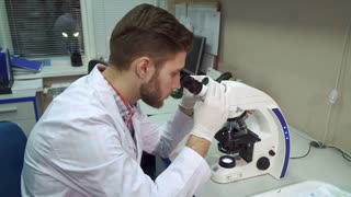 Handsome caucasian man moving stage clipse on the scope. Young male scientist working with microscope at the laboratory. Attractive bearded guy using optical lab tool