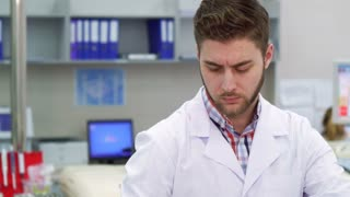Handsome caucasian man using computer at the laboratory. Young male scientist typing on keyboard at the lab. Close up of bearded guy in white coat doing his job