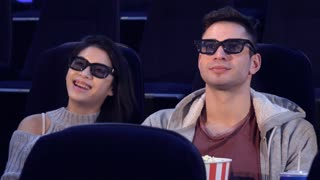 Handsome guy sitting between two attractive girls at the movie theater. Young caucasian man pointing his forefinger on the screen. Pretty brunette girl eating man's popcorn at the cinema