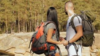 Hiking couple hugs near the cliff