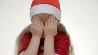 Kid girlin santa hat laughs