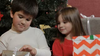 Kids look at their christmas gifts