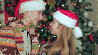 Loving couple dressed in sweater and scarf in Christmas decorated room