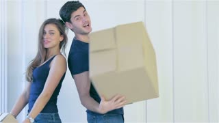 Loving couple enjoys a new apartment and keep the box in his hands