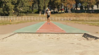 Male athlet has a bad landing after long jump