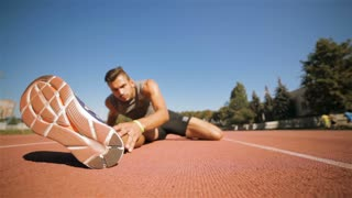 Male athlet stretches his leg at the stadium