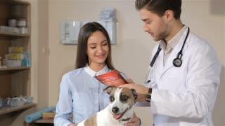 Male vet telling female dog owner about treatment for her dog. Attractive male veterinarian holding red pack of some dog treatment. Male vet doctor pointing his fingers on description of dog treatment