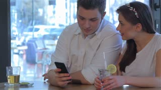 Man and woman looks at the smartphone