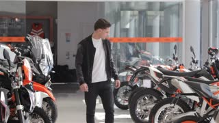 Man choose the motorbike at dealership