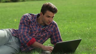Man lying on grass at park with laptop
