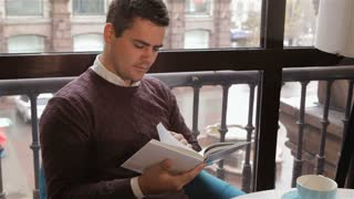 Man reads book at the cafe