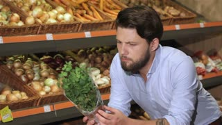Man smells basil at the supermarket