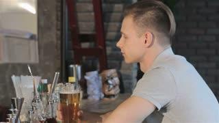 Man smiles after sip of beer