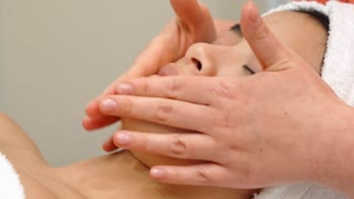 Massage specialist stroking girl's forehead at the beauty salon. Close up of female hands massaging woman's skin over brows and nose. Pretty asian client lying with closed eyes