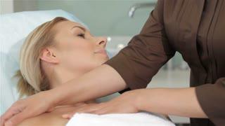 Masseur massages girl's shoulders