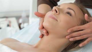 Masseur massages woman's chin