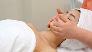 Masseur massaging girl's face at the beauty salon. Side view of female hands stroking cheeks and forehead of pretty asian client. Attractive brunette woman lying on massage chair