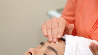 Masseur moisturizing female face at the beauty center. Cosmetologist preparing attractive asian girl for facial massage. Massage specialist applying oil on woman's face