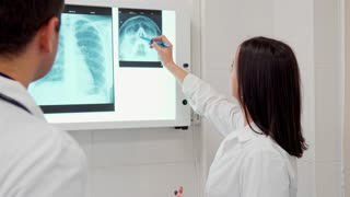 Mature female doctor pointing pen on the x-ray image of human head. Young brunette man in white coat standing backwards near his female coworker. Attractive caucasian female medic consulting with her